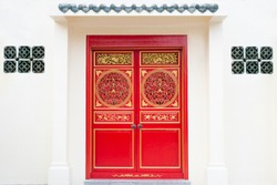 Chinese twin wooden doors in red and golden color on white wall.Asia entrance architecture.