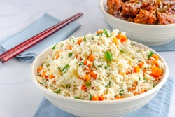 Chinese Vegetable Fried Rice in a Bowl with Side Dish and Chopsticks on White Background.