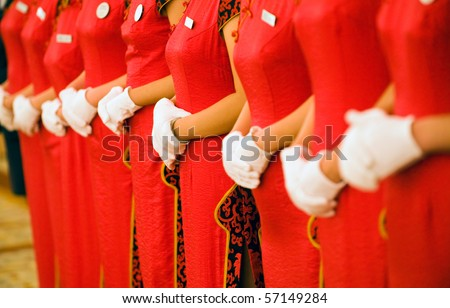 Chinese waitress dressed neatly in red cheongsam and white glove, standing  in a row. - stock photo