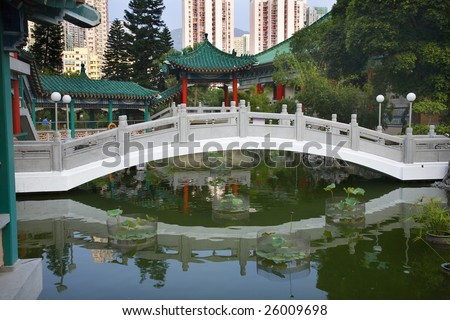 Chinese Water Garden Bridge and Reflection Amid Modern High Rise Buildings Wong Tai Sin Taoist Temple Kowloon Hong Kong