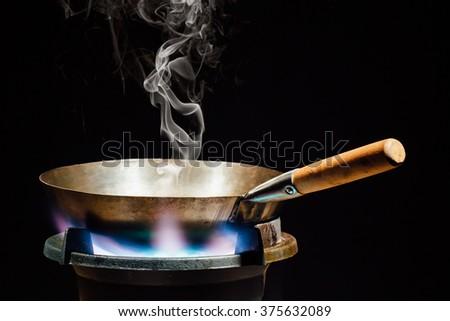 chinese wok pan on fire gas burner #375632089