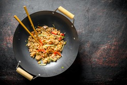 Chinese wok. Rice with vegetables and beef. On dark rustic background