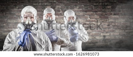 Chinese Woman and Team Behind In Hazmat Suites, Gas Masks and Goggles Against Brick Wall.