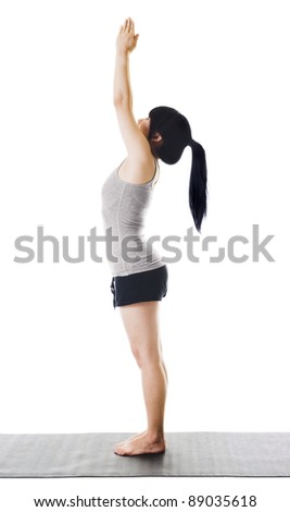 Chinese woman on a yoga mat doing the upward salute pose.