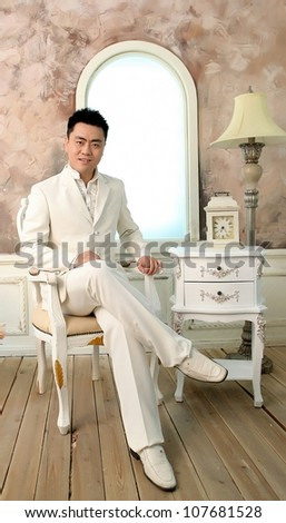 Chinese young man in white suite sitting in chair in bright room