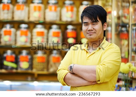 chinese young smiling male assistant seller in the traditional pharmacy shop  #236567293