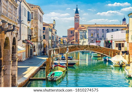 Chioggia cityscape with narrow water canal with moored multicolored boats, old buildings, brick bridge and tower of San Giacomo Apostolo church, blue sky in summer day, Veneto Region, Northern Italy Foto stock ©