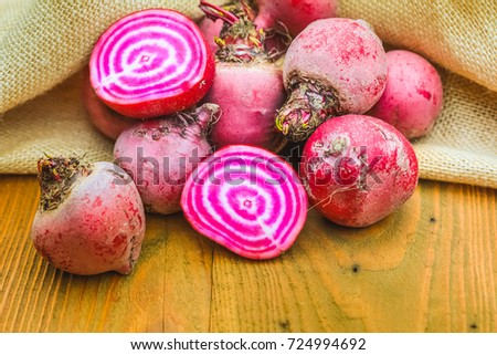 Chioggia striped or candy stripe beet whole and sliced in burlap sack on old rustic wooden table, selective focus