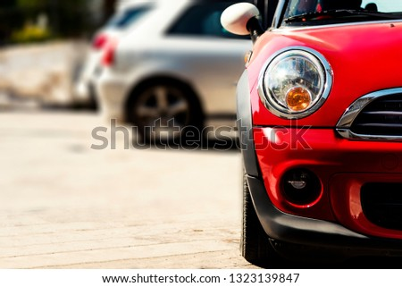 Chios, Greece - August 18, 2018: One had light of a Red Mini Cooper parked on the street. #1323139847