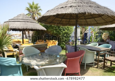 CHIPIONA, SPAIN - JULY 16, 2017: Colorful chairs in beach restaurant located in Chipiona, a municipality of the province of Cadiz, Andalusia, Spain #678982477
