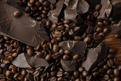 Chipped Dark Chocolate Pattern. Background of chocolate pieces and Coffee beans on a wooden background. Top view