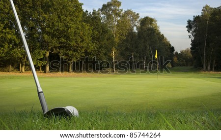 chipping a golf ball onto the green with golf club at dawn