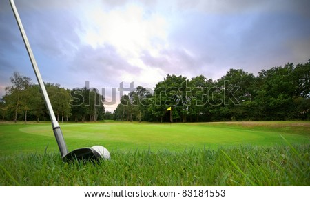 chipping a golf ball onto the green with golf club at sunset