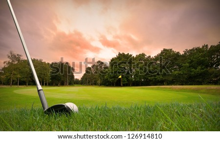 chipping a golf ball onto the green with golf club at sunset with copy space #126914810