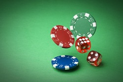 Chips and dices on green background close up