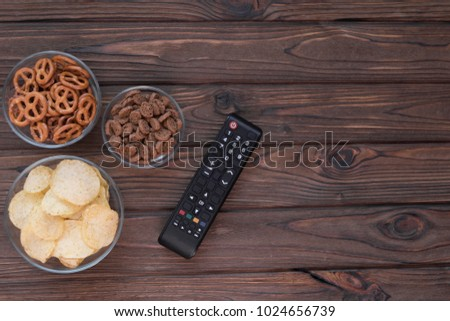 Chips, croutons, snacks. TV remote on the background of a wooden table. leisure. Leisure. #1024656739