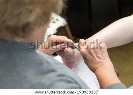 chiropodist gives a medical treatment at home