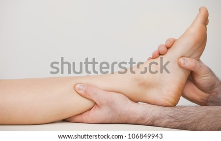 Chiropodist holding the ankle of a patient in his medical room