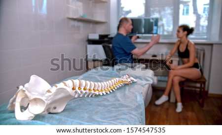 Chiropractic treatment - the doctor inspecting the young woman before the session - model of the human spine placed on the couch in the cabinet Foto stock ©