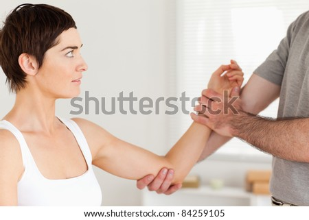 Chiropractor examining a woman's arm in a room