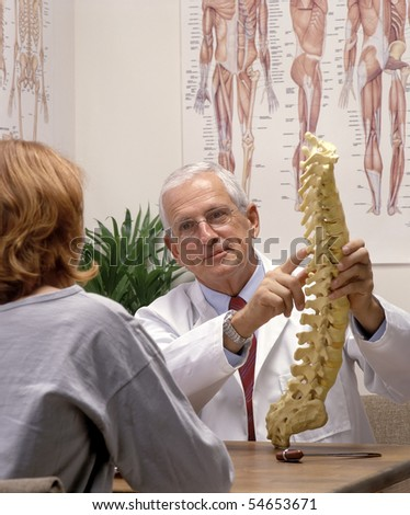 chiropractor showing a spine model to a patient