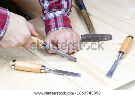 Chisels. Assortment of chisel of wood for carpentry. Hand holding chisel. A set of tools for wood processing. Stock photo ©
