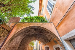 Chiusi, Italy street in small historic medieval town village in Tuscany summer with nobody orange colorful wall and arch vault passageway