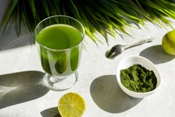 Chlorella detox healthy drink in glass with lime and powder on light background. Superfood, natural antioxidant for a green diet. Anti-aging effect. Hard shadows