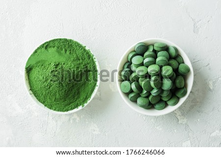 Chlorella or spirulina in the form of tablets and powder on a gray concrete background. Foto stock ©