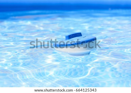 Chlorine tablet dispenser floating on the pool surface. Swimming pool cleaner.