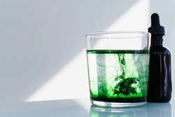 Chlorophyll drops in water, sitting next to dropper bottle in sunlight