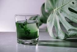 Chlorophyll extract is poured in pure water in glass against a white grey background with green leaf. Liquid chlorophyll in a glass of water. Concept of superfood, healthy eating, detox and diet