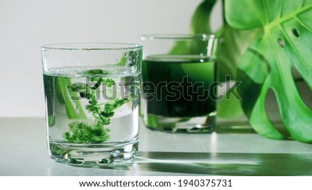 Chlorophyll extract is poured in pure water in glass against a white grey background with green leaf. Liquid chlorophyll in a glass of water. Concept of superfood, healthy eating, detox and diet Foto stock ©