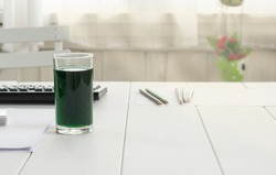 Chlorophyll in glass on table at home.