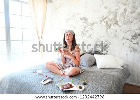 Chocoholic. Cheerful sad young craing woman eating sweets in her bedroom.  Emotional woman with eating icecream and crying after divorce