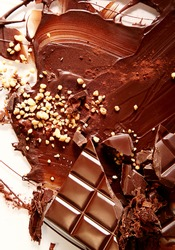 Chocolate abstract still life with melted chocolate smeared and sprinkled with chopped nuts and a chocolate candy bar with crumbs, overhead view
