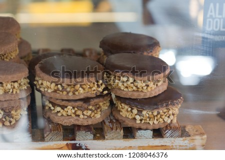 Chocolate alfajores, dulce de leche and mani stacked in showcase #1208046376