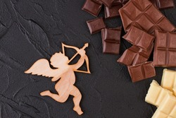 Chocolate and amour with arrow on black background.