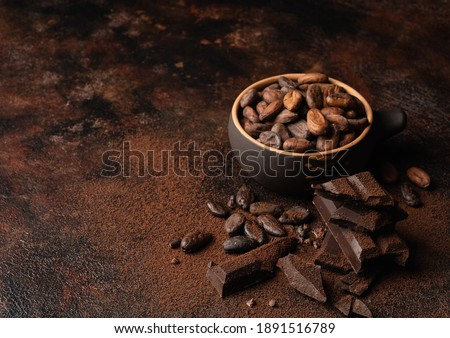 Chocolate and cacao concept. Cocoa powder in bowl near cocoa beans and broken chocolate on black background