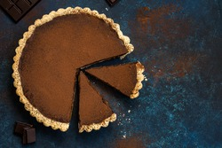 chocolate and caramel tart on dark blue background. top view