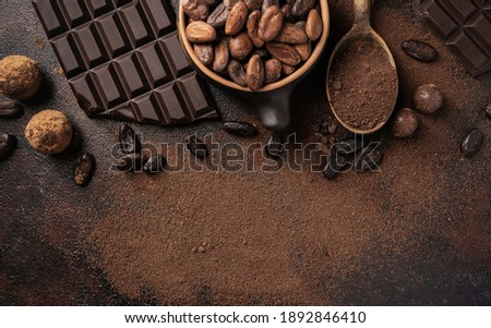 Chocolate and cocoa concept. Cocoa powder in a spoon near cocoa beans and broken chocolate on a black background