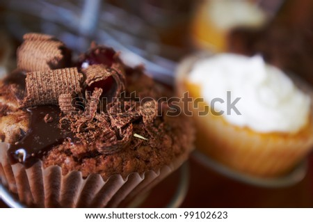 Chocolate and cream filled cupcakes with glazed cherries and chocolate shavings on a display stand. Shallow Depth of field with focus on the chocolate cupcake
