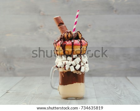 Chocolate and donuts extreme milkshake with marshmallow and other sweets in mason jar on gray wooden background. Crazy freakshake or overshake on gray wooden table with copy space