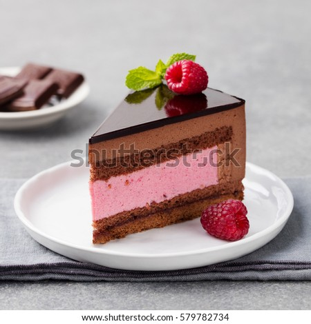 Chocolate and raspberry cake, mousse dessert on a white plate. Copy space.