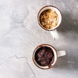 Chocolate and vanilla caramel mug cakes from microwave over grey texture background. Top view, copy space. Square image