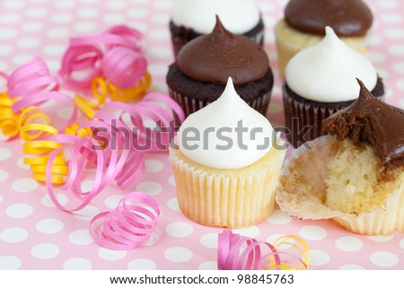 Chocolate and vanilla cupcakes with curled party ribbons on a polka dot background -- one cupcake is partly eaten