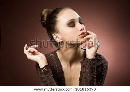 Chocolate art, artistic portrait of beautiful young brunette with bonbons.