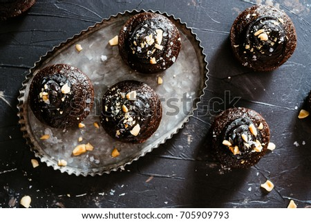 Chocolate avocado cupcakes with chocolate vegan buttercream frosting, topped with peanuts on a silver tray on a dark black, moody surface.