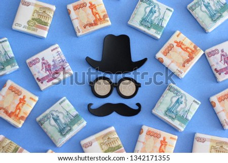 Chocolate banknote 5000, 2000, 1000 rubles on a colored background. Reflection. Nominal cost. Symbolic sweet food. Silhouette of a man, hat, glasses, mustache and Russian money 1 ruble in  the eyes #1342171355