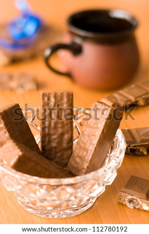 Chocolate bar and chocolate wafers with pot and ribbon on the table